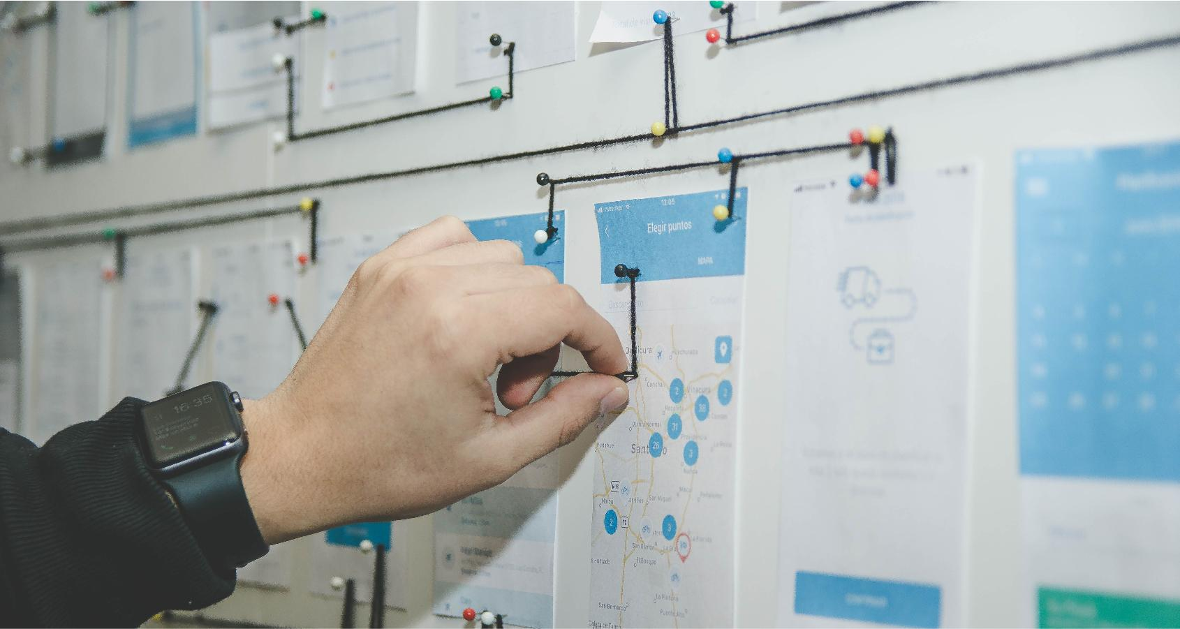 A designer uses pins and prints to determine the enterprise application UX design.