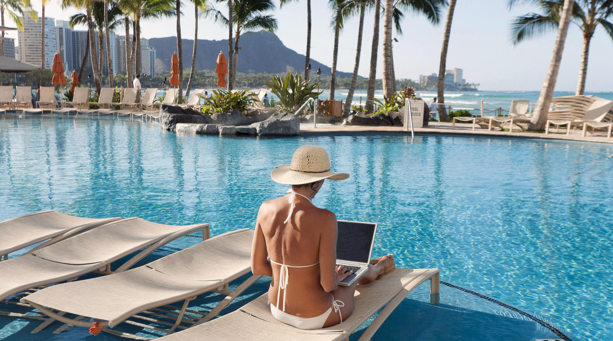Freelance designer digital nomad remote working at a pool.